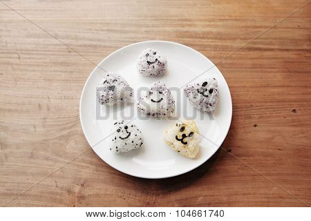 Onigiri rice balls with smiley faces, made with cut out nori seaweed on white plate.
