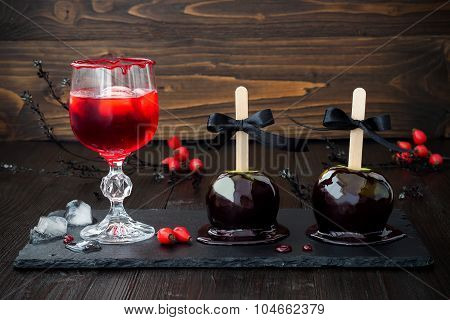 Red bloody vampire cocktail and black poison caramel apples. Traditional dessert recipe for Hallowee