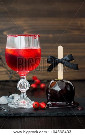 Red bloody vampire cocktail and black poison caramel apple. Traditional dessert recipe for Halloween
