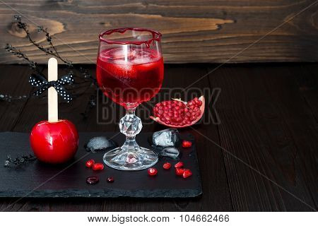 Spooky bloody cocktail and red caramel apple. Traditional dessert and drink recipe for Halloween par