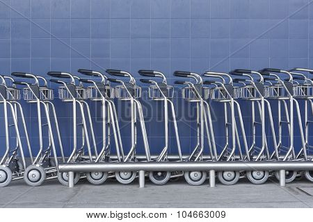 Airport Trolley Parking Lot With Empty Trolleys And Blue Wall