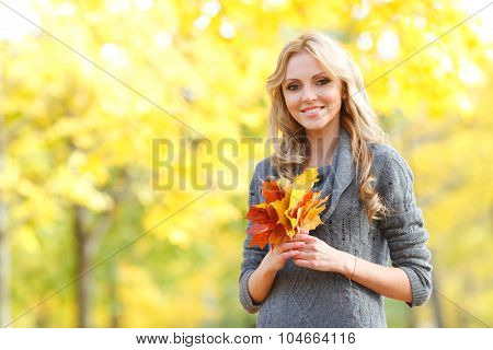 Portrait of a beautiful blond smiling woman in autumn forest