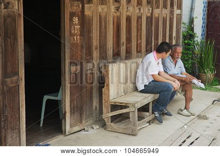 Tour guides sit at the entrance to one of the hostels in Chiang Khan, Thailand.