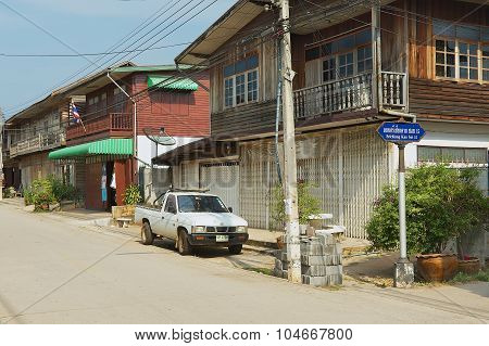 View to the street with traditional residential buildings in Chiang Khan, Thailand.
