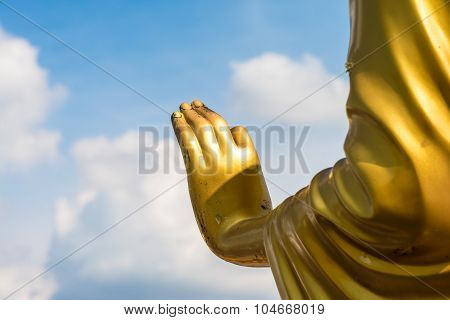 Golden Buddha Hand On 'o.k.' Sign (peace) With Blue Sky And Clouds Closeup Focused On  Hand