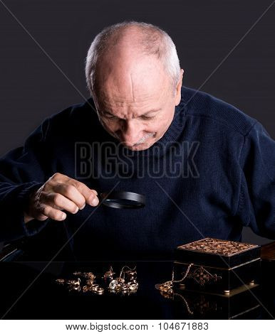 Senior Jeweler  Looking At Jewelry