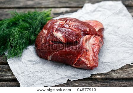 Raw Ox Cheek On Crumpled Paper,  Decorated With Dill. On Old  Wooden Table