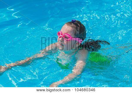 Cute girl swim in the pool