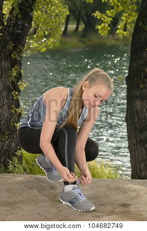 Young Beautiful Blonde Woman Tying Sport Shoe Laces Outdoors