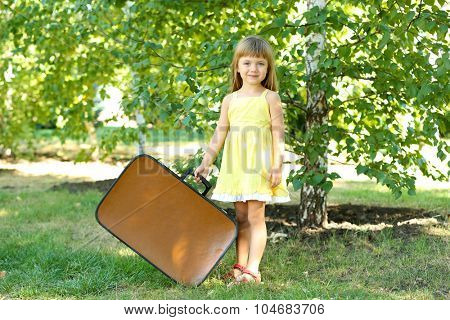 Little girl with suitcase on grass in park