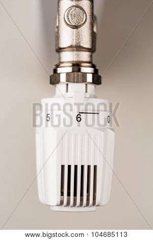 the thermostat of a radiator is on full blast. high room temperature cause high energy costs