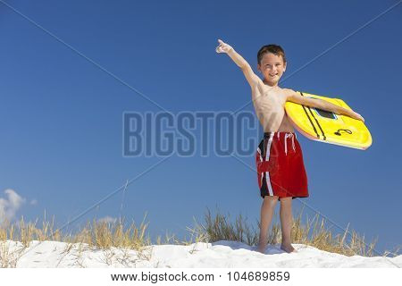 Young male boy child with yellow surfboard on a beach with bright blue sky