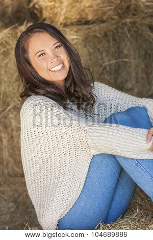 Beautiful happy Asian Eurasian young woman or girl smiling sitting in sunshine on a hay bale in a barn