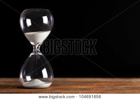 Hourglass on wooden table on black background
