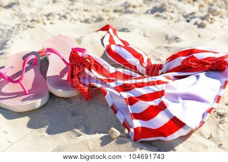 Flip flops and swimsuit on beach sand closeup