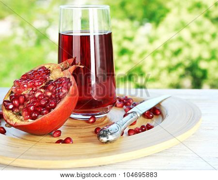 Fresh garnet juice with fruit on bright background