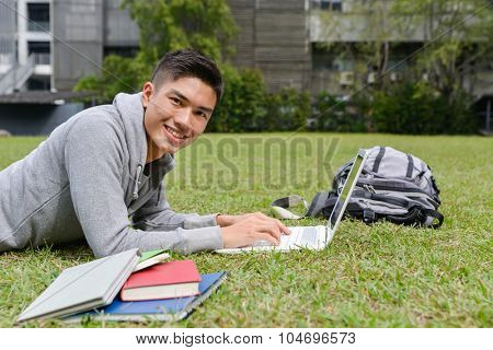 Portrait of asian student use laptop lying on a grass at a campus