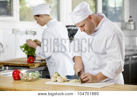 Two professional chefs preparing vegetables in large kitchen