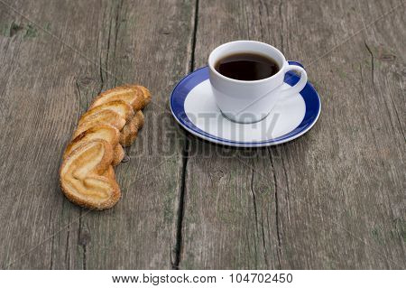 Cup Of Coffee On A Saucer With A Blue Border And Cookies In A Row