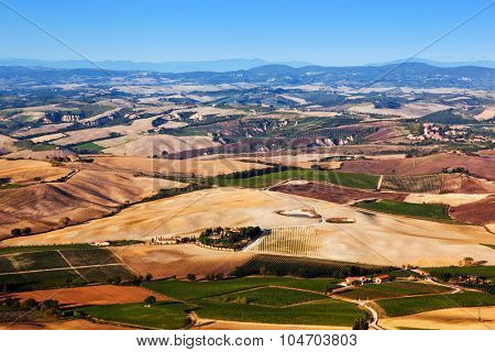 Tuscany landscape panorama with blue sky. Typical for the region tuscan farm houses, hills, vineyards. Italy