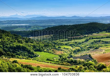 Tuscany landscape full of green meadows, forests, fields on picturesque hills. Italy