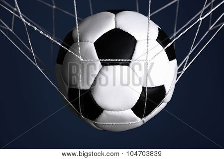 Soccer ball in the net on blue background