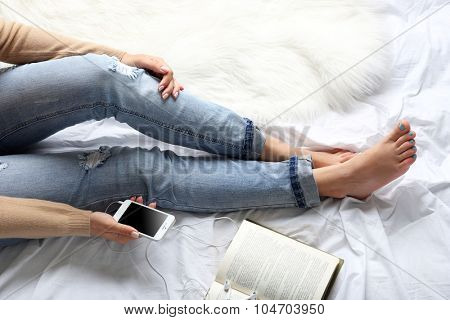 Woman in blue jeans watching phone on bed top view point