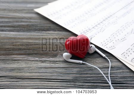 Earphones with red heart and music notes on wooden background