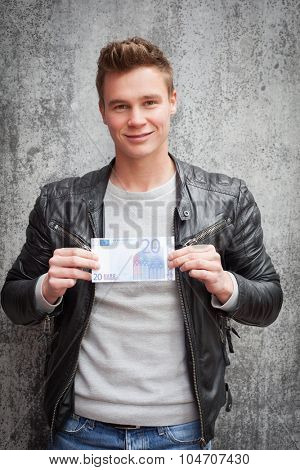 Attractive young guy holding twenty euro note