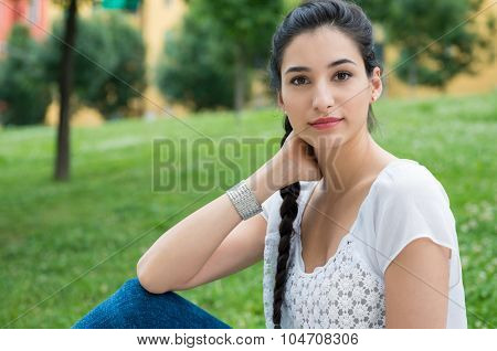 Closeup shot of young woman looking at camera. Happy girl sitting at the park. Shallow depth of field with focus on student with braid hair looking at camera.