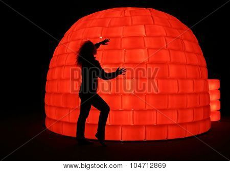 MOSCOW - OCT 10, 2014: Woman (with model release) standing near the buildings in the form of igloo with red illumination at the Festival Circle of Light in Moscow