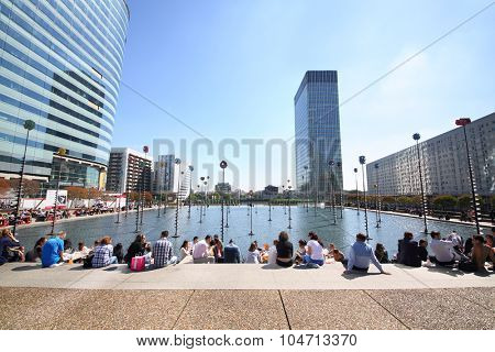 PARIS, FRANCE - SEP 12, 2014: A lot of people sitting on the steps in front of a swimming pool on the esplanade of La Defense in Paris