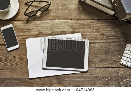 blank tablet and phone placed on an wooden desktop workspace