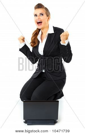 Excited modern business woman sitting on floor with laptop and rejoicing her success