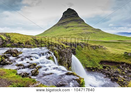 Iceland - the country of mountains, the rivers and falls. Cascade deep falls Kirkyyufell Foss on the grassy mountains