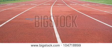 White And Yellow Lines And Arrow. Textured Red Rubber Of Running Racetracks In Outdoor Stadium