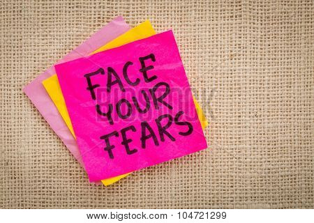 Face your fears advice or reminder on a sticky note against canvas