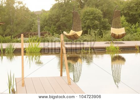 The image of chaise-longues around the pond outside