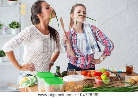 Women preparing healthy food playing with vegetables in kitchen having fun concept dieting nutrition