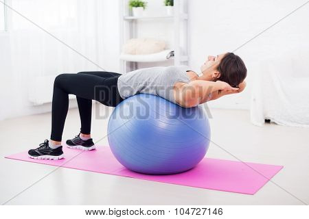 Fitness young woman doing abdominal crunches on fit ball.