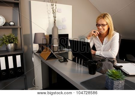 Happy blonde businesswoman sitting at desk, using laptop computer.