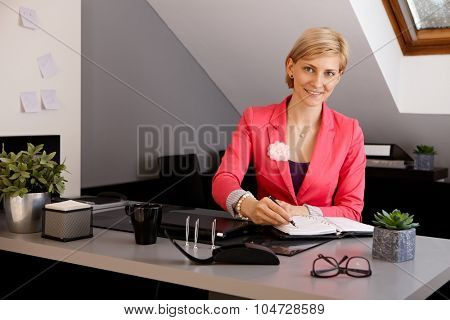 Young businesswoman sitting at desk in office, writing notes to personal organizer, smiling, looking at camera.