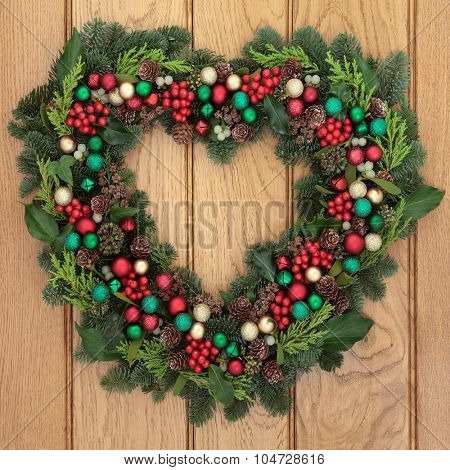 Christmas heart shaped wreath with bauble decorations, holly, mistletoe and winter greenery over oak  front door background.