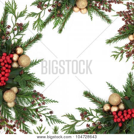 Christmas flora with gold bauble decorations, holly, ivy, fir and winter greenery over white background.