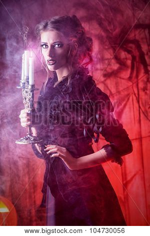 Beautiful girl in medieval dress in a mysterious abandoned house. Witchcraft, witch. Halloween concept.