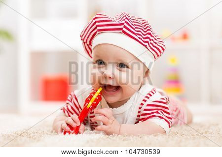 Cute baby in hat on the bed having fun