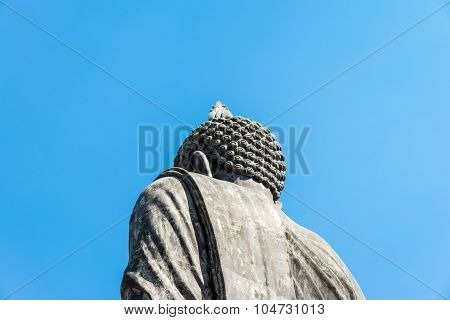 Buddha Statue  From Back View Sculpture With Ok Hand  Sign With Deep Clear Blue Sky On Sunny Day In