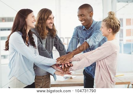 Smiling business team putting their hands together at office