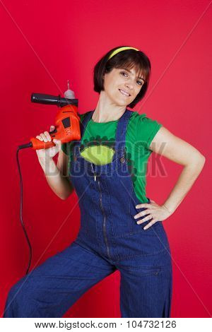 Happy woman holding an electric drill