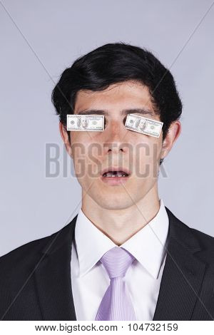 Young businessman with little dollar bills covering his eyes